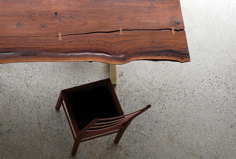 오스카퍼니처 가구 전시장에 클라로월넛 테이블과 송아지 가죽으로 만든 등받이가 긴 의자가 놓여있다