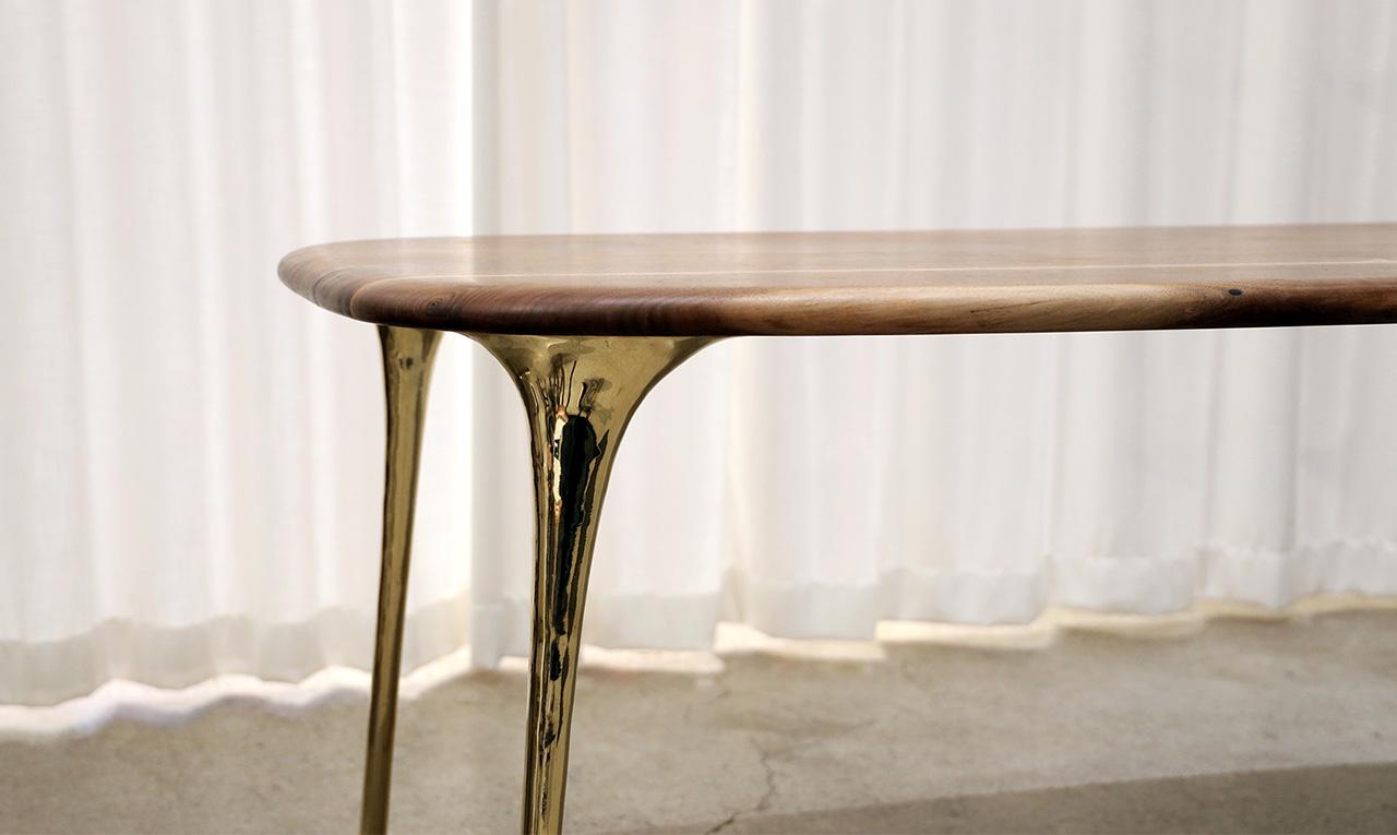 하얀 바탕의 스튜디오에서 월넛과 황동으로 만든 테이블이 전시되어 있다.