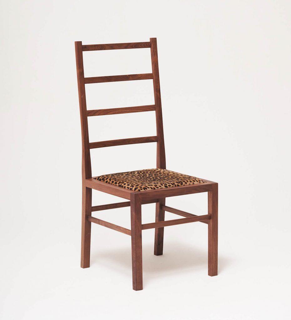 등받이 높이가 높은 의자에 송아지 가죽으로 만든 쿠션이 있는 의자이다.