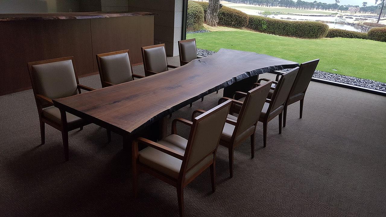 골프장 로비에 세팅된 대형 블랙월넛 우드슬랩 테이블의 사진